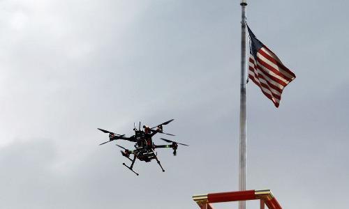 A drone in flight near the American flag.